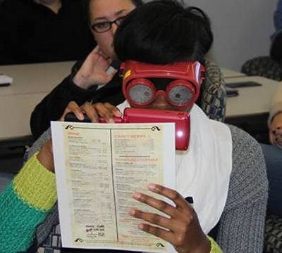 See different participant using vision simulator glasses and a magnifying aid.
